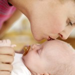 Woman Kissing the Top of a Baby's Head (3-6 Months)